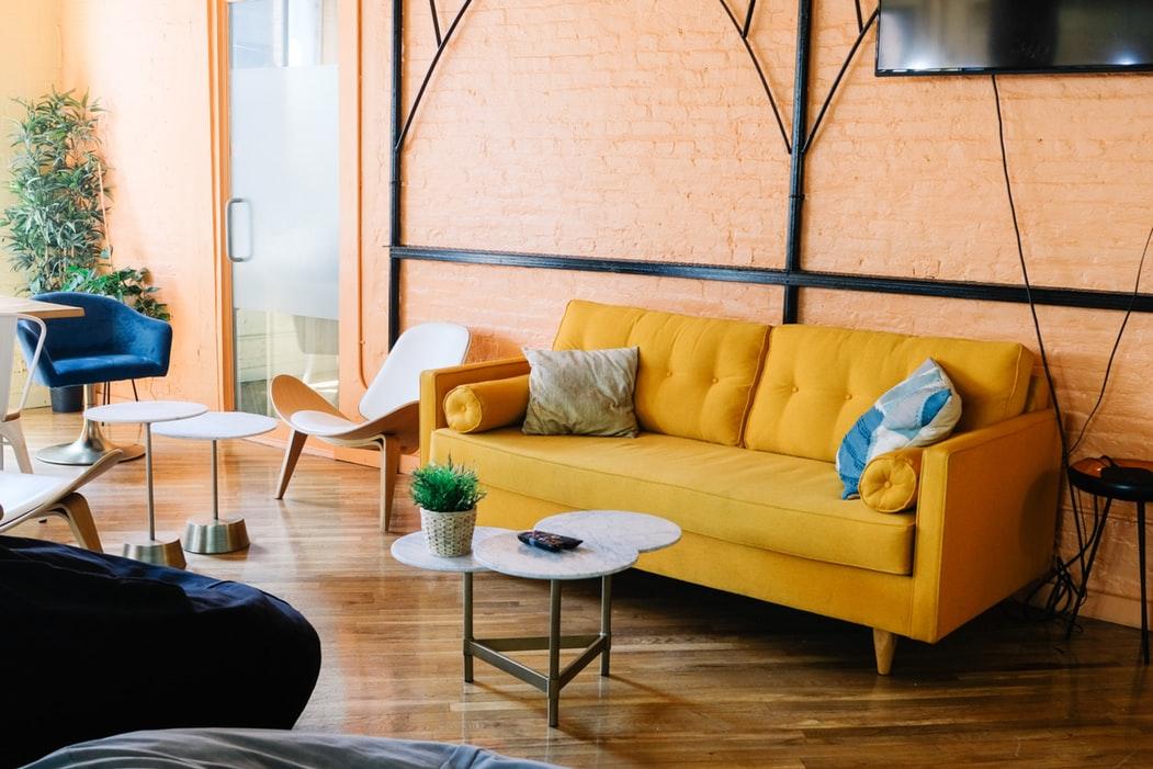 مبل راحتی چرمی زرد دیوار صورتی گلبهی دکورتسیون مدرن